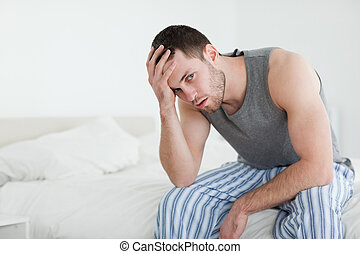 Young man sitting on his bed