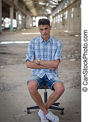 Young man sitting on office chair in abandoned warehouse