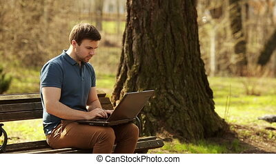 Young Man Sitting On Park Bench Using Laptop