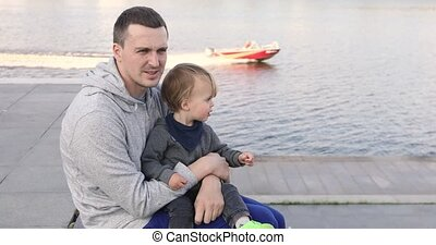 Young man sitting on pier with baby