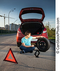 man sitting on road and leaning against broken car