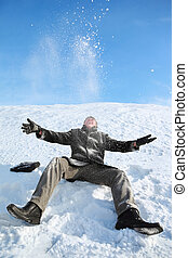Young man sitting on snow and throw him upwards  and makes merry