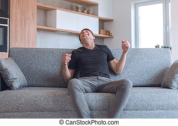 young man sitting on sofa in cozy living room