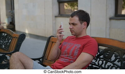 Young man sitting on the park bench talking on the mobile phone