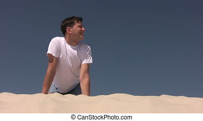 Young man sitting on the sand