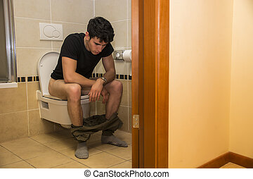 Young Man Sitting on Toilet