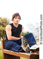 Young Man Sitting on Wooden Bench