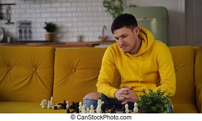 Young man sitting on yellow sofa and playing chess in room. Male playing in logical board game with himself