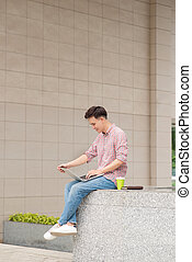 Young man sitting with laptop outside the office