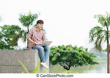 Young man sitting with laptop outside the university building