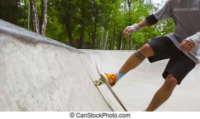 Young man skateboarding at outdoor skate park - Slow motion,...