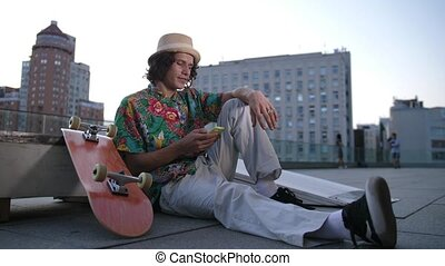 Young man skater sharing in social media on phone - Close-up...