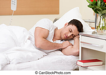 Young man sleeping in a hospital bed