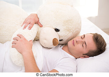 Young man sleeping in bed with big teddy bear