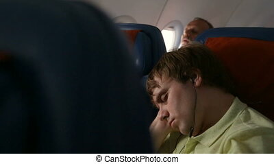 Young man sleeping in the airplane