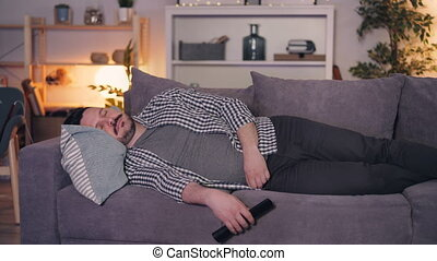 Young man sleeping on couch at home holding remote control...