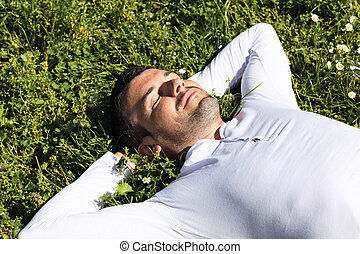 young man sleeping on the grass in a park