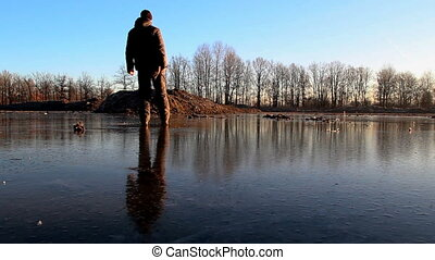 Young man slide, skate on small pond ice