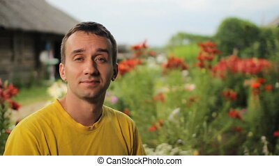 Young man smiles near flowers in the garden. Against the...