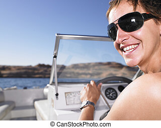 Young Man Smiling and Driving Boat