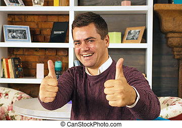 Young man smiling and showing two thumbs up