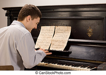Young man smiling as he plays the piano
