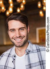 Young man smiling at camera at the cafe