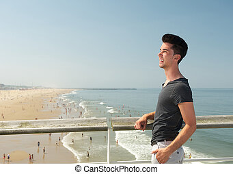 Young man smiling at the beach