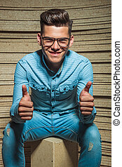 young man smiling in studio while showing positive gesture