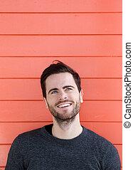 Young man smiling on orange background