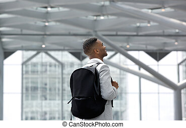 Young man smiling with bag at airport