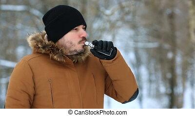 Young man smokes an electronic cigarette in winter closeup.