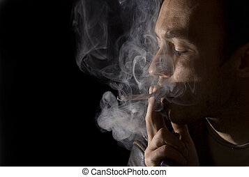 Young man smoking a cigarette, copy space left