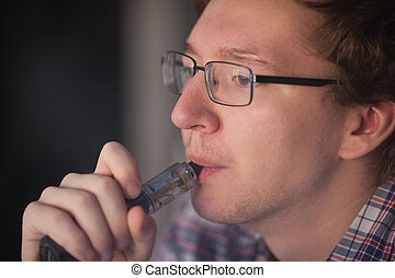 Young man smoking electronic cigarette near window.