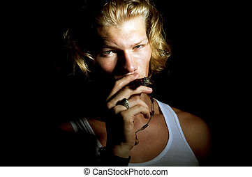 young man smoking over a black background