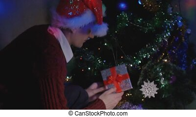 Young man sneaking up to Christmas tree and placing a gift