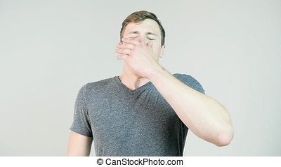 Young man sneezing on a white background, slow motion.