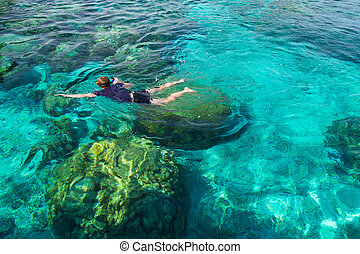 Young man snorkeling over coral reef in transparent tropical sea, Rok island, Thailand