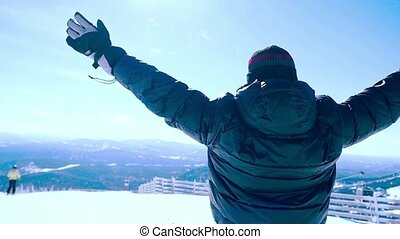 Young man snowboarder rises hands in Mountains in slowmotion...