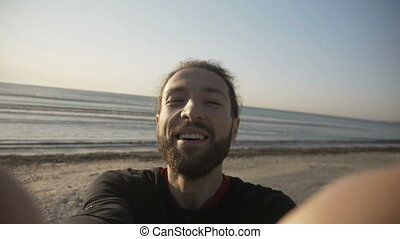 Young man social media influencer having fun and having a video call at beautiful sunset on the beach in slow motion