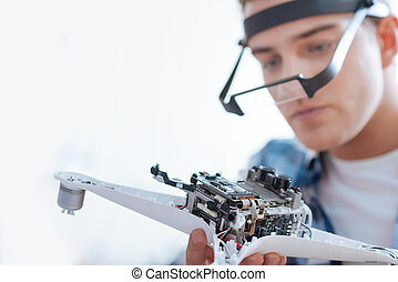 Young man soldering a drone detail