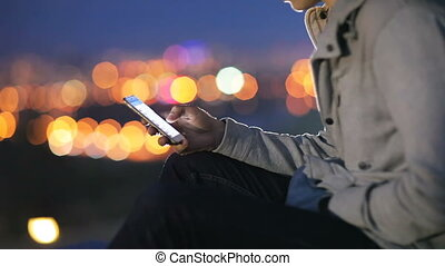 Young man speaks on social networks on the background of the city at night