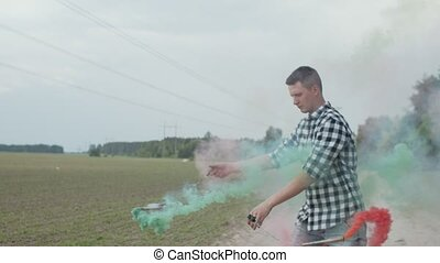 Portrait of handsome male walking in cloud of colored smoke spinning poi with smoke bombs outdoors. Skillful man in checkered shirt going on dusty road in veil of colorful fume in summer nature.