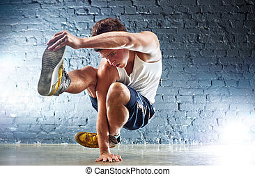 Young man sports exercises. On wall background.