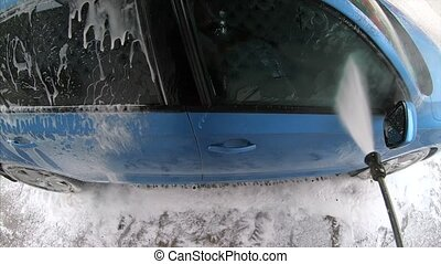 Young man spraying down his car with soapy water using a...