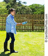 young man spreading lawn fertilizer