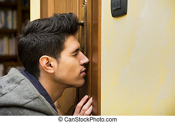 Young man spying through the keyhole of a door standing with his eye pressed up against the wood as he tries to see what is going on inside