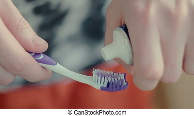 man squeezing toothpaste on the brush - young man squeezing...
