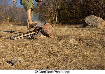 Young man stamping out a fire