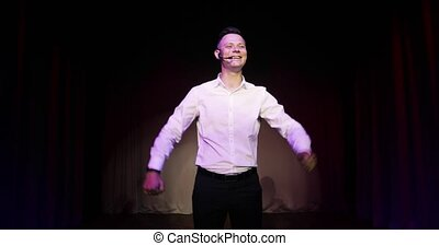 Young man stand up comedian speaking jokes in micropphone standing on stage.